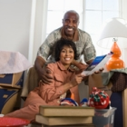 Happy African-American couple sitting on floor near moving boxes.
